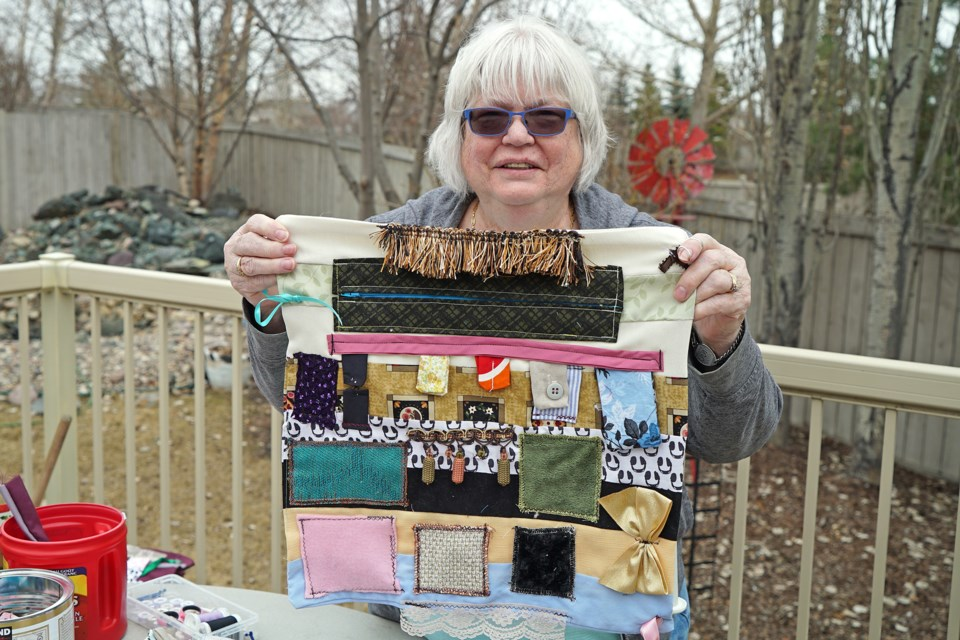 Willa Bosch holding up one of her special lap quilts at her home in St. Albert. Willa donates these quilts to patients at the Sturgeon Community Hospital. BRITTANY GERVAIS/St. Albert Gervais
