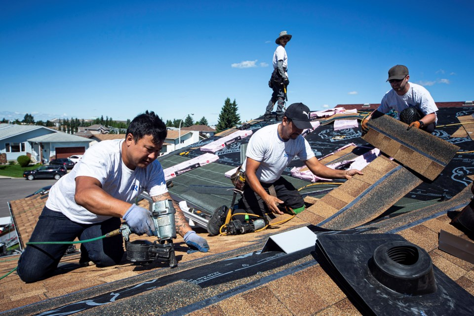 Crew members from Roe Roofing & Exteriors in St. Albert once again volunteered to replace a roof for a deserving family, this time in Edmonton, on Friday. CHRIS COLBOURNE/St. Albert Gazette