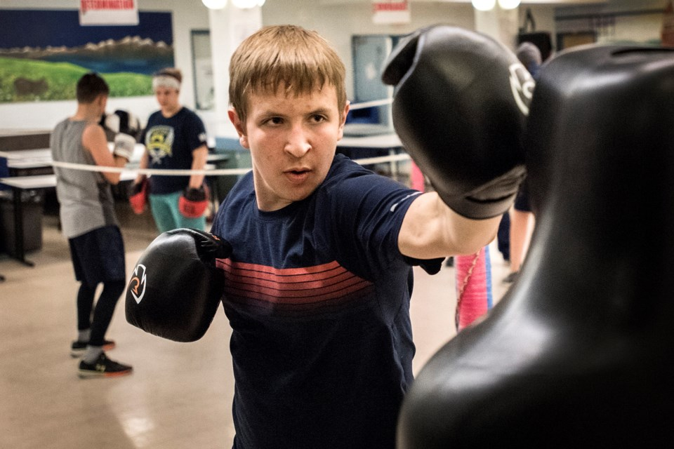 PUNCHER – Reid Pidsadowski of the St. Albert Boxing Academy works on the dummy bag at Wednesday's training session at Sir George Simpson School. In the background are Jacob Wiwchar and Susan Haas. The St. Albert academy is hosting a Boxers Against Bullying club card next Saturday at 2 p.m. at St. Albert Community Hall.