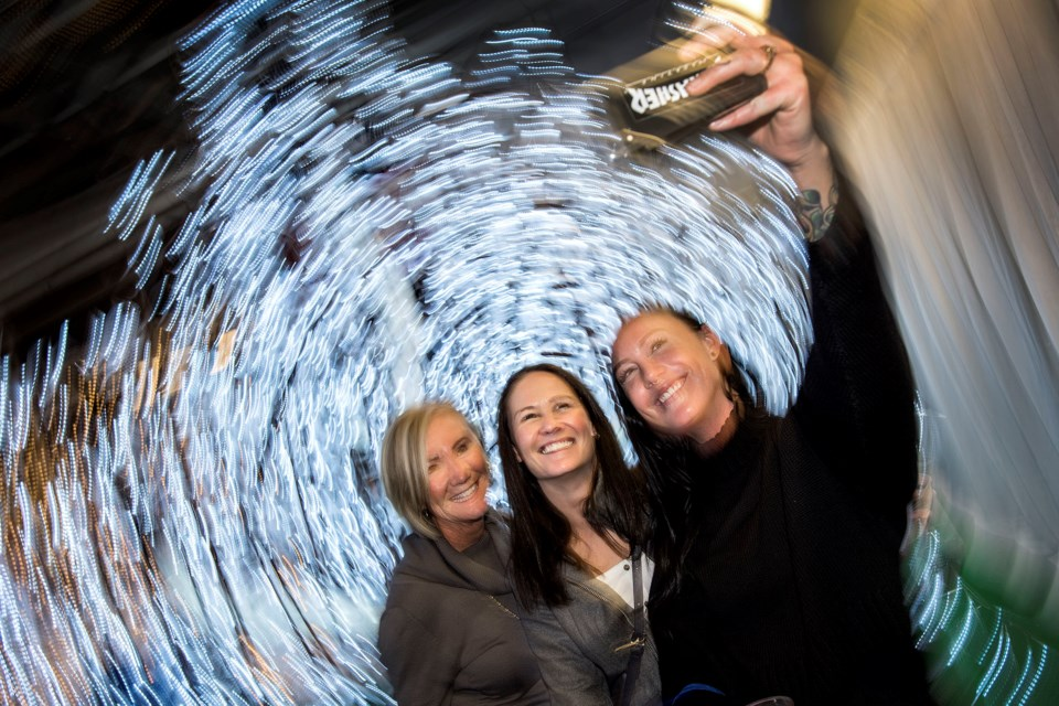 Anne Winnington, left, and two of her daughters Allison Winnington and Kathleen Winnington, right, take a selfie of themselves in the Enchanted Forest of the Enjoy Light Festival during VIP night at the Enjoy Centre in St. Albert November 21, 2019. A slow shutter speed and turning of the camera by the photographer creates the effect behind the ladies.   DAN RIEDLHUBER/St. Albert Gazette