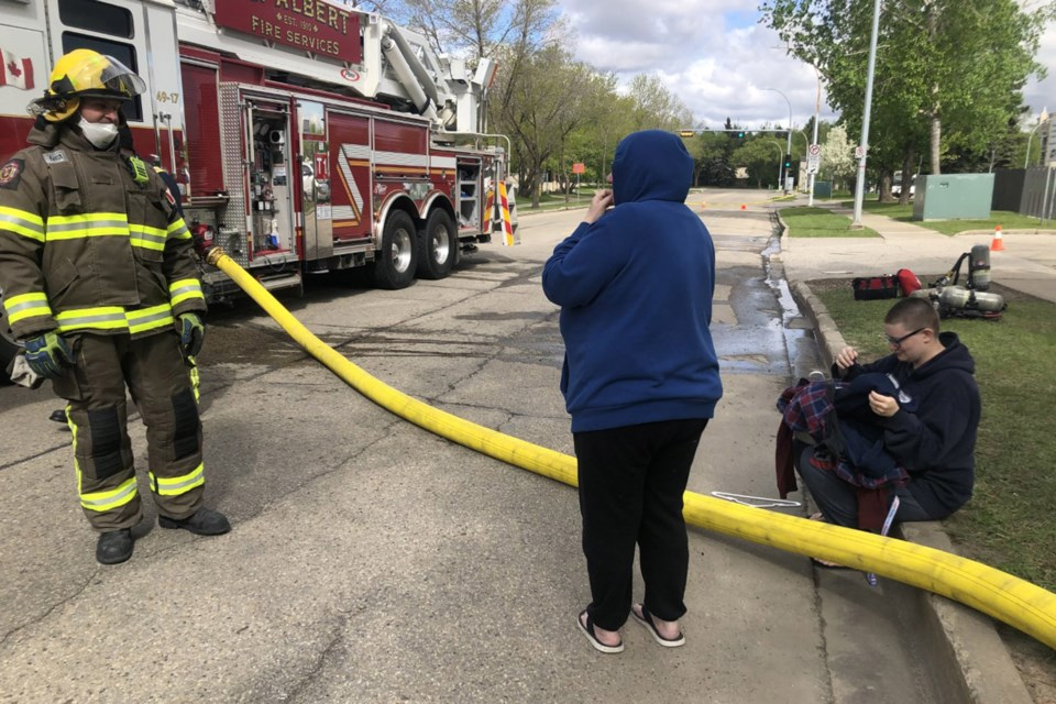 Denise and Chelsea (right) thank a St. Albert firefighter for bringing some clothing from their apartment suite. The two left with nothing but the clothes on their back and the family cat after realizing there was a fire. BRITTANY GERVAIS/St. Albert Gazette
