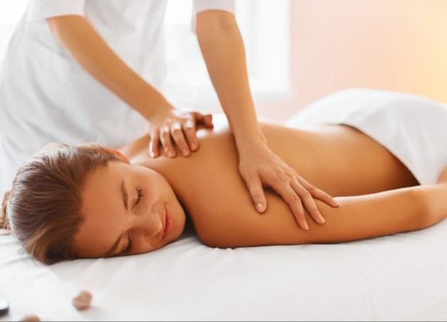 Spa treatment. Woman enjoying relaxing back massage in cosmetology spa centre. Body care, skin care, wellness, wellbeing, beauty treatment concept.