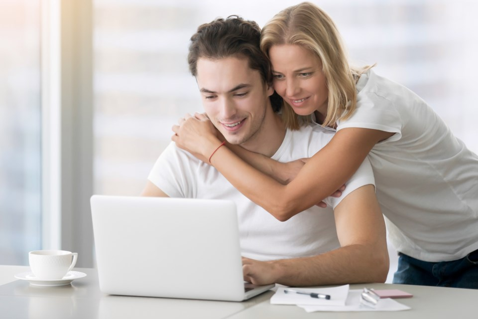 4-young-happy-couple-with-laptop-PBUA6YS
