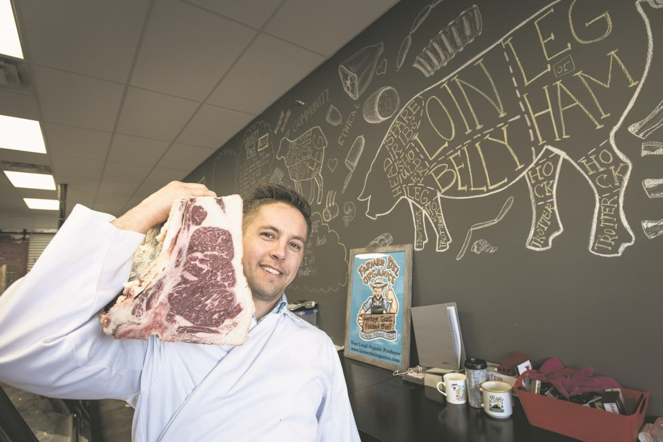 Kyle Iseke, owner of Darcy's Meat Market, shoulders a large piece of Wagyu beef behind the counter of his Campbell Park store in St. Albert in April  2018. FILE PHOTO/St. Albert Gazette