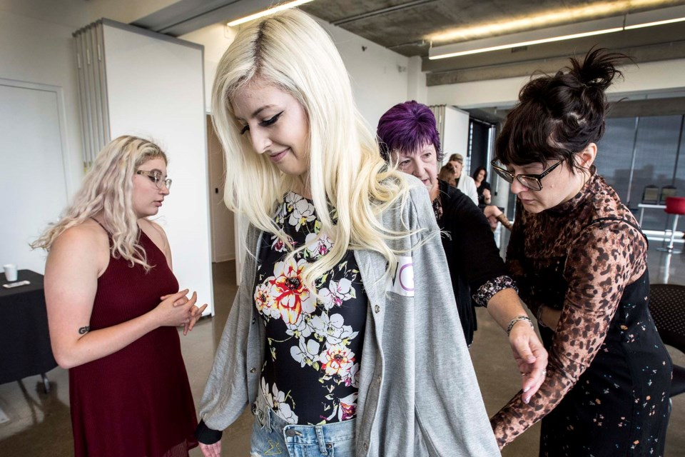 Local clothes designer Becky Boyd, left, stands by while one of the fashion show entries is scrutinized by Marni Walker and Alisha Schick, right, fashion instructors, at the college in Edmonton on Aug. 16, 2019. Modelling the Whiskey Girls ensemble is fellow MCC student Sarah Adams. DAN RIEDLHUBER/St. Albert Gazette