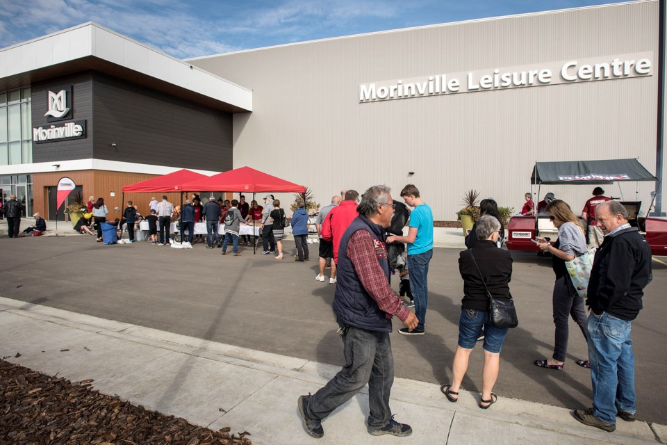 Patrons line up to take advantage of the free barbecue.  DAN RIEDLHUBER/St. Albert Gazette