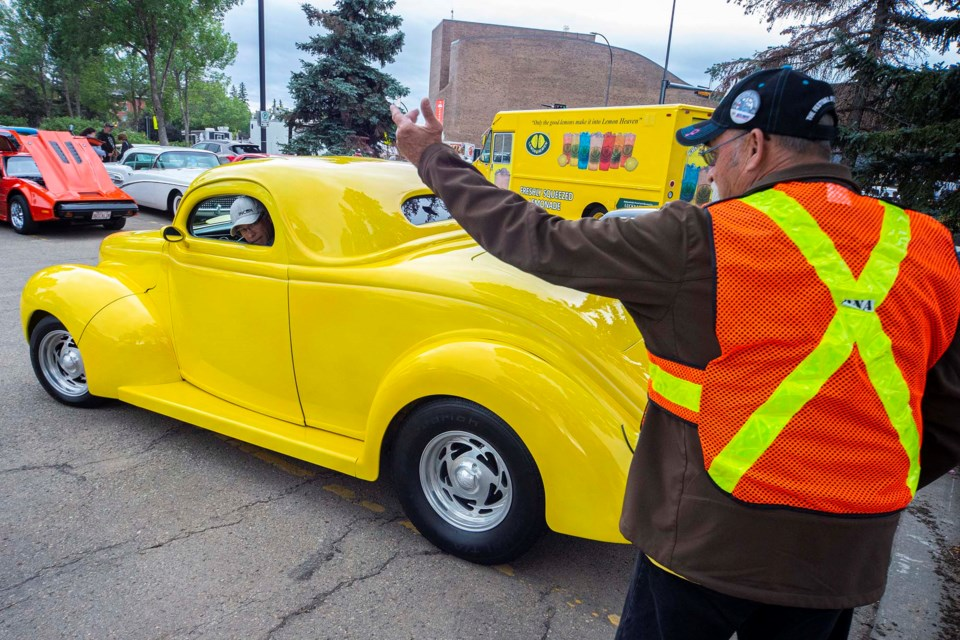 Gary Warren, right, a St. Albert Cruisers member helps direct Dave Jolivette's 1936 coupe into place as classic cars filled up the downtown for the annual car show and street dance on Friday night as part of Rock'n August celebrations. CHRIS COLBOURNE/St. Albert Gazette