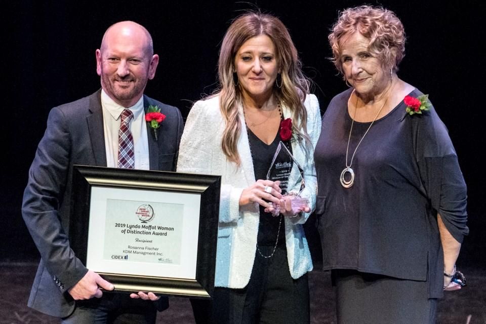Rosanna Fischer, centre, of KDM Management Inc., receives the Lynda Moffat Woman of Distinction award from Lynda Moffat, right, and Mark Stoneleigh, Chamber of Commerce chair.  DAN RIEDLHUBER/St. Albert Gazette