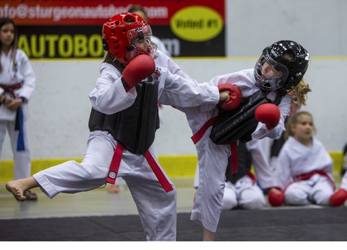 COMBATANTS – Evelyn Brown, left, and Annika Harris exchange strikes and kicks in the red belt female 6 to 8 sparring division at the 21st annual Spirit of the North, hosted by the Desa School of Karate at Servus Credit Union Place. The two-day event featured 280 competitors and 89 divisions in kata, kumite (sparring) and kobudo (weapons training) for ages six to adult from white belts to black belts. CHRIS COLBOURNE/St. Albert Gazette