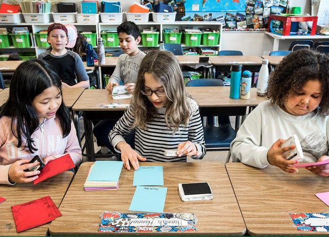 From left, Brielle Lomibao, Natalya Rudan and Taya McInneis, Grade 5 students at Leo Nickerson Elementary School, work on thank-you cards for volunteers recently. Their teacher, Andrea Daly, used the creative project to promote the benefits of volunteerism.