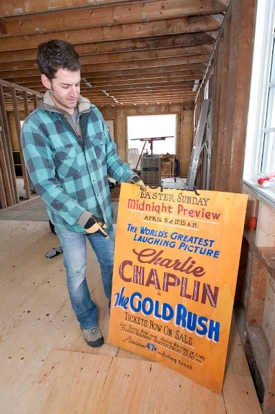 GREAT AD. BAD INSULATION – Energy efficiency expert Stuart Fix displays a 1940s-era movie poster he found in the walls of his Edmonton home during renovations. Homes from