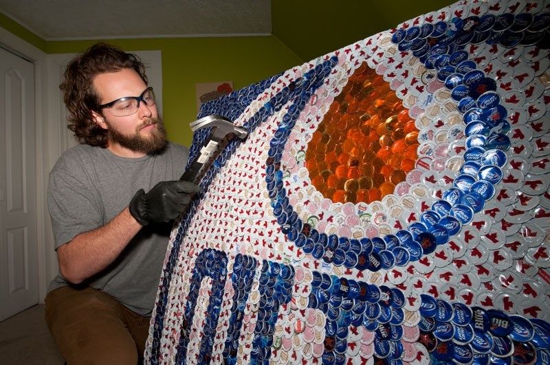 FINISHING TOUCHES – Former St. Albert resident Jeff Meszaros hammers some edges flat on a large Edmonton Oilers mural he made from bottlecaps. Meszaros collects the caps and