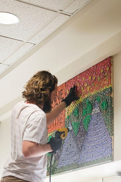 Bottle cap artist Jeff Meszaros installing his newest creation at Bonnie Doon Shopping Centre at the end of February.