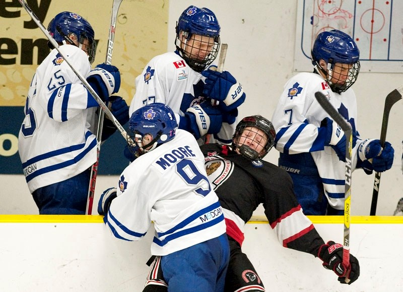 CRUNCHED – Lleyton Moore of the Toronto Marlboros slams Jayden Grubbe of the Calgary Bisons into the Toronto bench during Thursday's game at the John Reid Memorial
