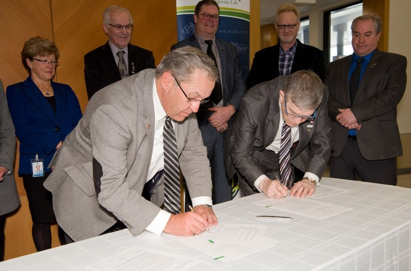 ANNEXATION AGREEMENT — Mayors Tom Flynn and Nolan Crouse sign a memorandum Tuesday at the Sturgeon County office. The memo commits their respective governments to negotiating