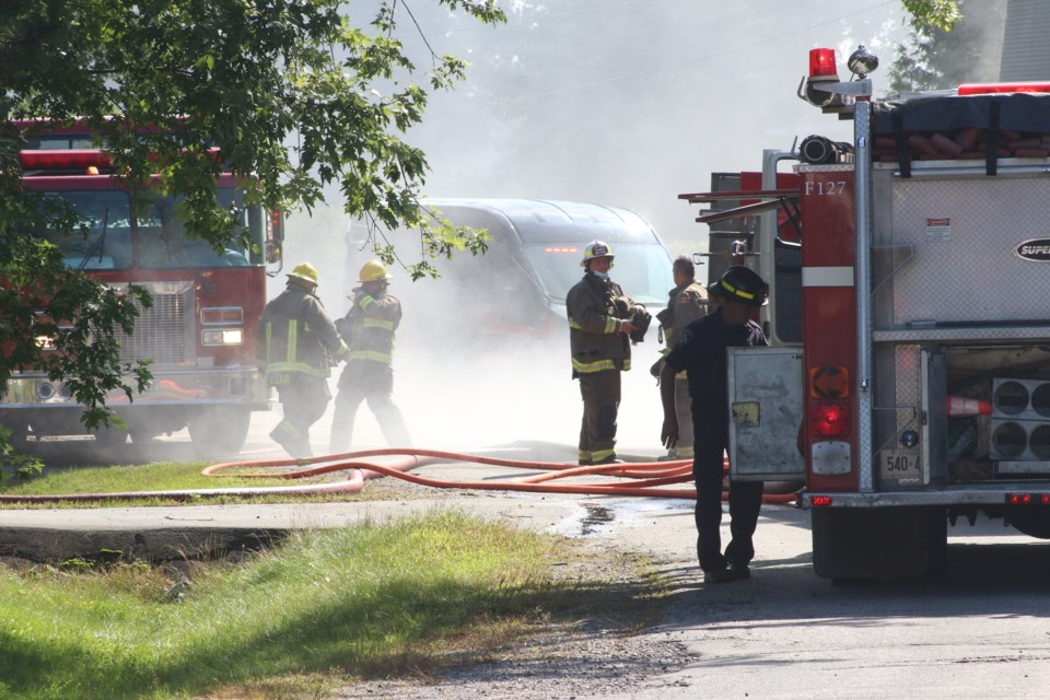 Firefighters walk through thick smoke from a house fire on Velma Street in Val Caron this morning.