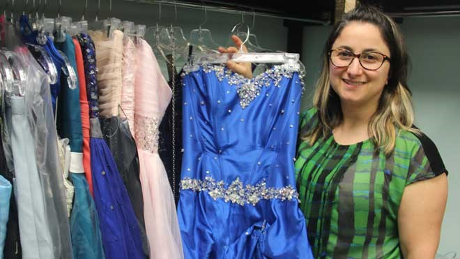 Sudbury Women's Centre executive director Giulia Carpenter, seen in this 2018 file photo, shows off some of the formal dress donations the women's centre received. Those dresses are being offered free of charge for those in need. (File)