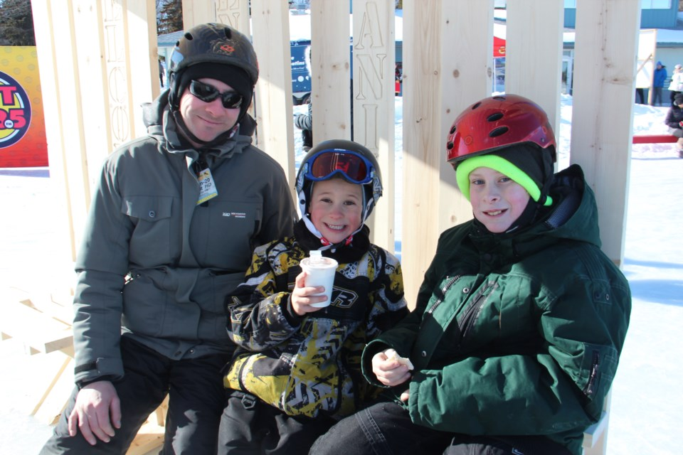 Dale Kelly and sons Jonathan, 7, and Nicholas, 11, enjoyed some hot chocolate and snacks Feb. 8 while resting in an ice station created by McEwen School of Architecture students. (Heidi Ulrichsen/Sudbury.com)