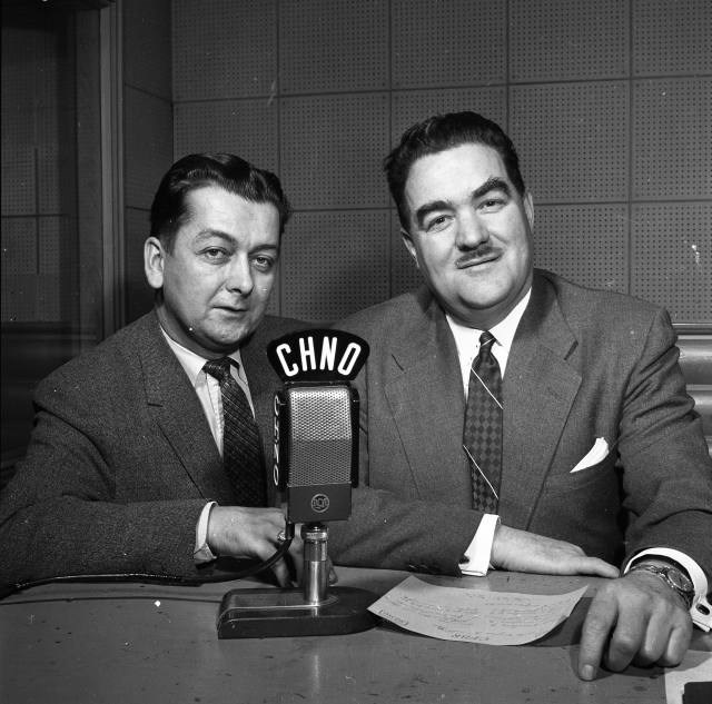 Baxter Ricard (right), owner and manager of radio stations CHNO AM and CFBR AM, with station manager René Riel on the first CFBR went on the air. (City of Greater Sudbury Archives)