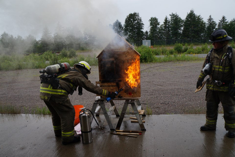Greater Sudbury Fire Services firefighters give a demonstration using a model on how homes burn. (Jenny Lamothe/For Sudbury.com)