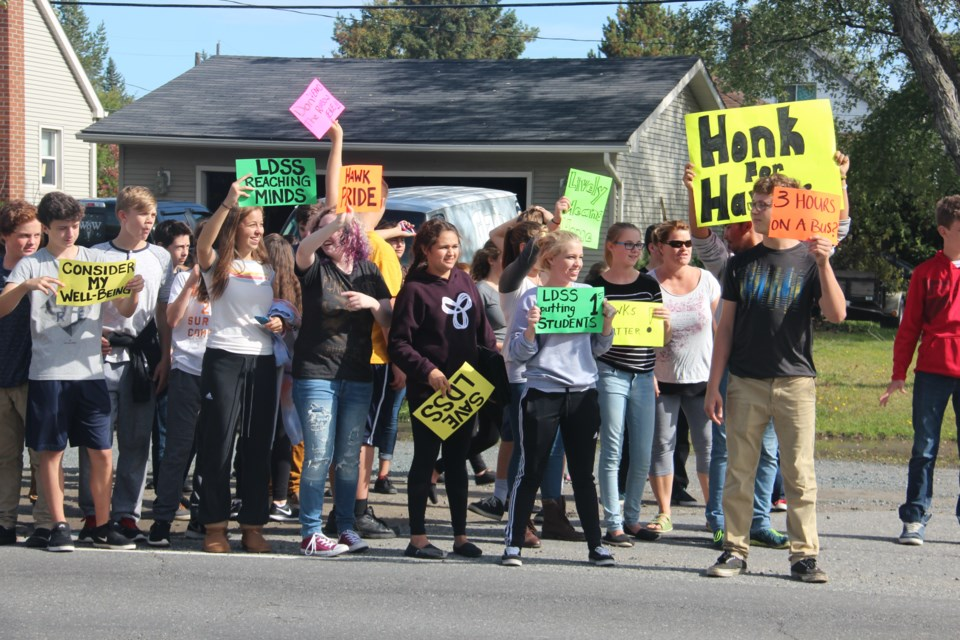 Lively District Secondary School students stand on the site of the road Thursday afternoon, holding up signs of support for their school, which may close as soon as next fall. About 200 students at the school staged a walk-out to protest the board's plans. Photo by Heidi Ulrichsen.