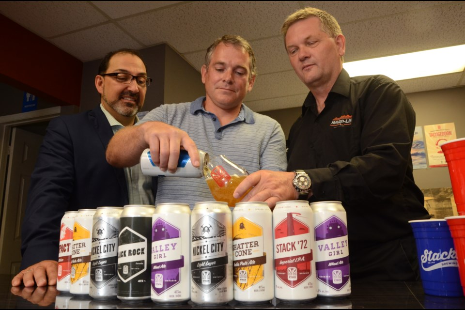 Stack Brewing owner Shawn Mailloux, centre, pours a glass of Saturday Night with Sudbury MPP Glenn Thibeault, left, and Hard-Line Solutions president Walter Siggelow following a Northern Ontario Heritage Fund Corporation funding announcement on Friday. Photo by Arron Pickard