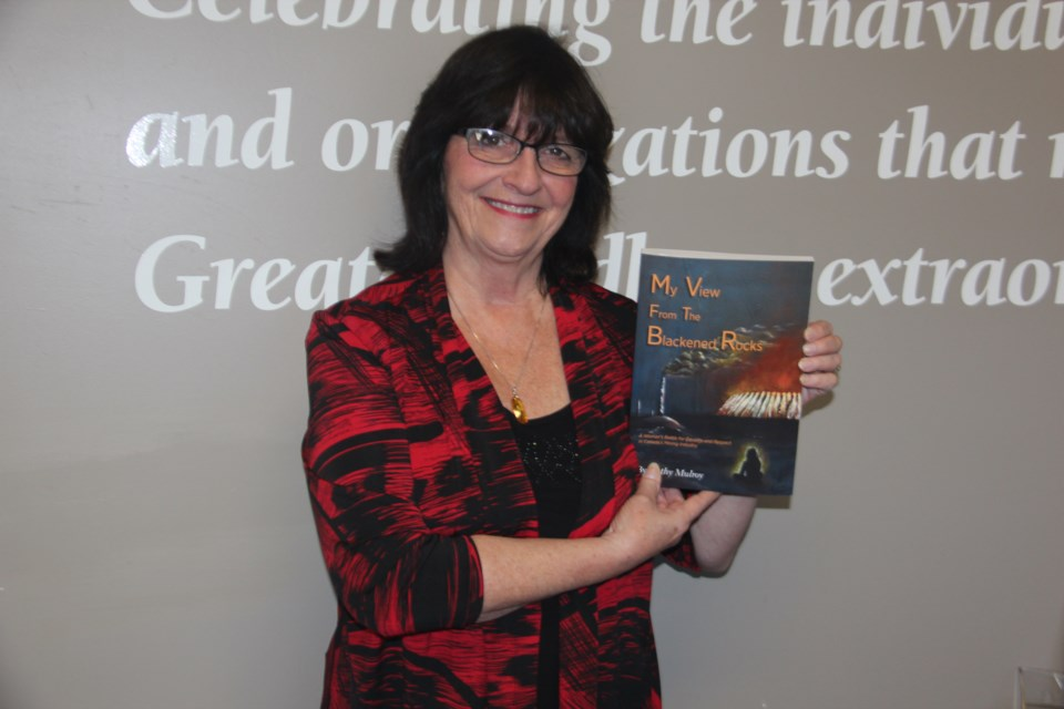 "Cathy Mulroy with her book ""My View from the Blackened Rocks."" (Heidi Ulrichsen/Sudbury.com)"