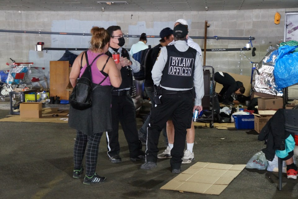 Outreach workers with the Poverty and Housing Advocacy Coalition were on hand to help relocate around 30 people from a homeless encampment in the YMCA parking lot downtown after city bylaw officers and police moved in to evict them May 12.
