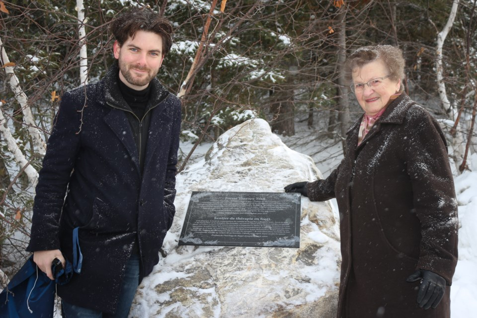 """Lea Curridor, wife of the late Giuseppe """"Beppi"""" Curridor and Students' General Association president Eric Chappell, show off the plaque dedicating Beppi's Forest Therapy Trail. (Heidi Ulrichsen/Sudbury.com)"""