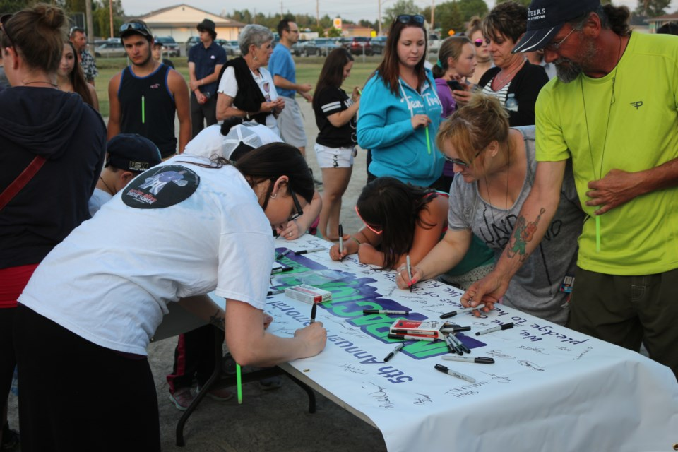 Supporters sign the banner at the Impact 6/21 memorial walk on Sunday evening. Photo by Darren MacDonald