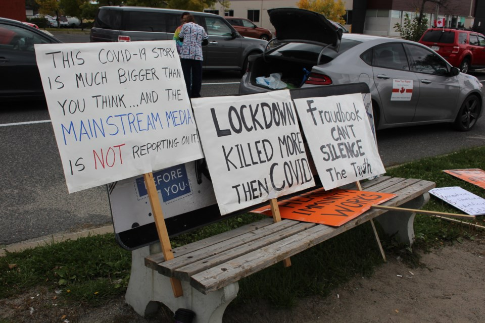 Several of the anti-mask protesters' signs sit on a bench on Lasalle Boulevard. (Heidi Ulrichsen/Sudbury.com)