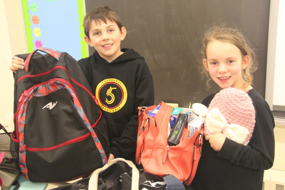 Logan MacIlroy and Mackenzie Moore show off some of the bags their Grade 4 class at Cyril Varney Public School collected for the Fill a Purse for a Sister Campaign. (Heidi Ulrichsen/Sudbury.com)
