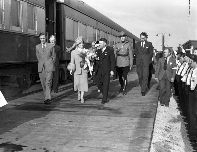 King George VI and Queen Elizabeth walking beside their train with Capreol Mayor James E. Coyne, various dignitaries and Mounties in Capreol. A crowd is gathered to greet them including military personal. (Sudbury Star Fonds, City of Greater Sudbury Archives)