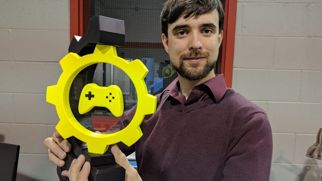 Mike Daoust, the organizer of the Sudbury Game Design Challenge, poses with a 3D-printed trophy that will go to the winning team on Jan. 15. The competition will pit 20 multi-disciplinary teams from Northern Ontario against each other to build a video game in 48 hours. Photo by Jonathan Migneault.