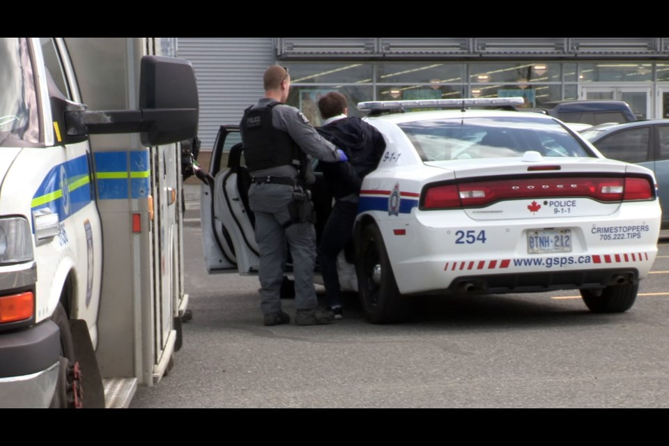 Alexander Stavropoulos is placed into the back of a police car on June 3, 2019, after a random attack on a mother and infant in the parking lot of a retail location on Marcus Drive in Sudbury. (Heather Green-Oliver / Sudbury.com)