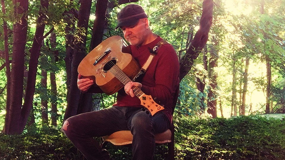 Singer-songwriter David Leask holds Voyageur, a guitar handmade with pieces of Canada's history and culture, including a piece of Wayne Gretzky's hockey stick, wood from John A. Macdonald's house, and an Inuit ulu knife. (Supplied)