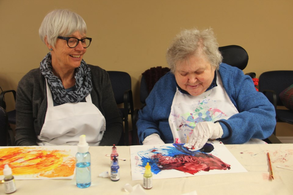 Jen Cawley-Caruso (left) watches her friend of 30 years, L'Arche Sudbury resident Audrey Penn, create an art piece as part of the Sage and Time Art Project. (Heidi Ulrichsen/Sudbury.com)