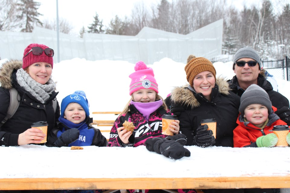 (From the left) Amanda Tessier with her son Rylan and daughter Emma, sitting beside Crystal Lanthier, her son Bryson Elms and her husband Greg elms, at Bell Park's Snow Day (Keira Ferguson/ Sudbury.com)