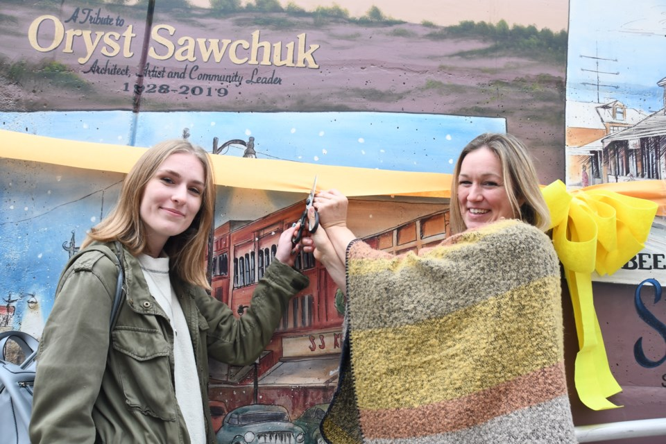 Lauren Calson (left) who assisted professional artist Monique Legault (right) with the creation of a mural honouring the late Oryst Sawchuk, in the underpass connecting Elgin Street and Riverside Drive. (Marg Seregelyi/ Sudbury.com)
