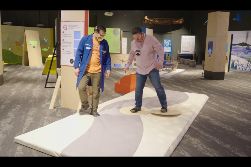 Waubgeshig Rice tries out some snowshoes with the help of Matthew Graveline at Science North's new exhibit, Indigenous Ingenuity: Timeless Inventions.