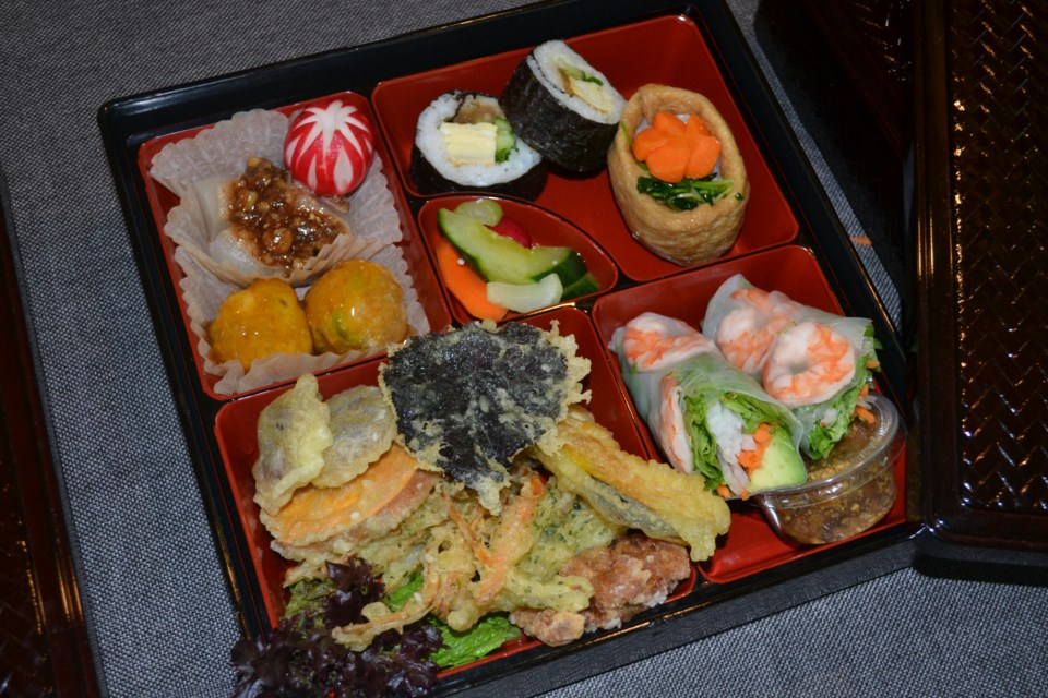 A sample bento box features rolls, tempura, beautifully crafted daikon summer radishes and pumpkin squash balls. These boxes are recyclable and refillable when ordered from the Nickel Refillery.
