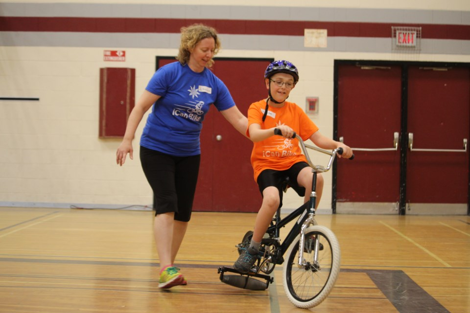 Liam MacIntyre, 10, learns how to ride a two-wheel bicycle with help from physiotherapist, Penny Jacob, at this year's iCan Bike Program, hosted by HSN's NEO Kids Children's Treatment Centre. (Heather Green-Oliver/Sudbury.com)