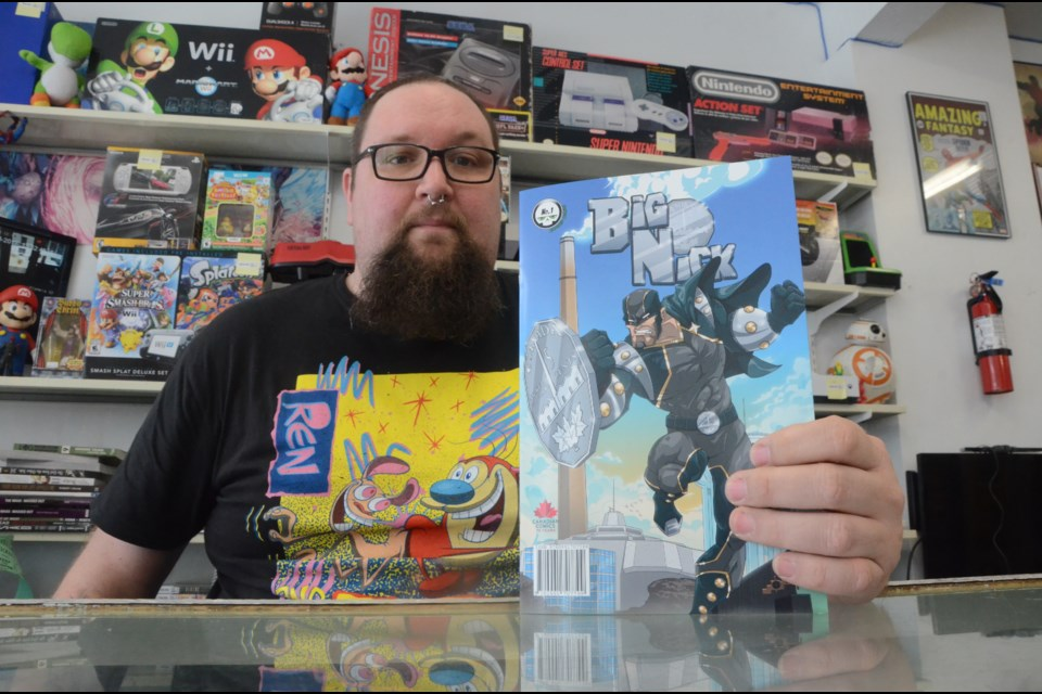 Cal Abram from Comics North (holding a copy of the Big Nick comic) wants to give you cool prizes for contributing to the Sudbury comic book shop's food bank campaign. (File)