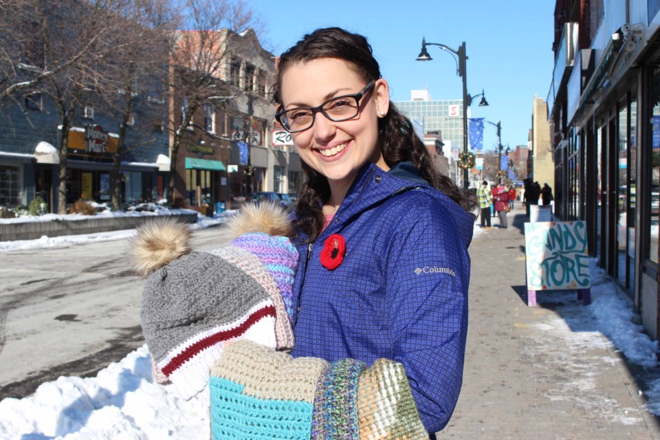 Samantha McAuliffe distributes 50 hats, headbands and scarves in Downtown Sudbury for those in need. (Keira Ferguson/ Sudbury.com)