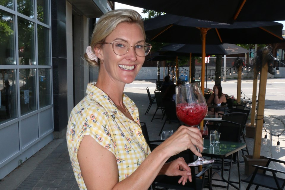 Staying hydrated in the shade is part of the advice being offered this week by Public Health Sudbury and Districts. Ainslie Loney was being cool in the shade at a downtown Sudbury patio with a refreshing summer smoothie. (Len Gillis / Sudbury.Com)