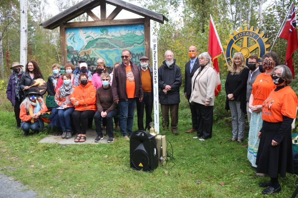Rotarians and their guests celebrate the unveiling of one of four new peace poles that have been planted in Rotary Park.