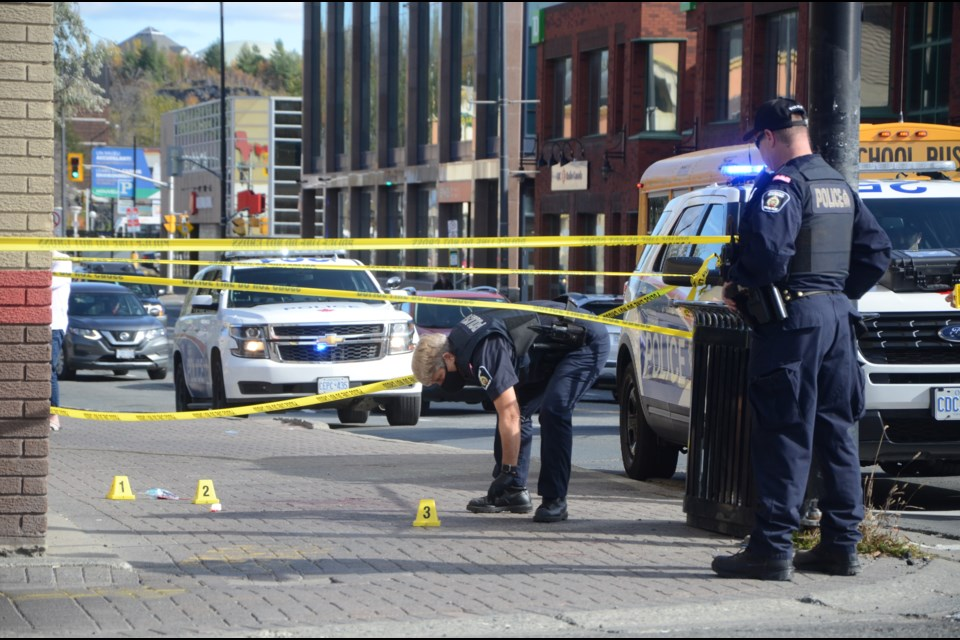Evidence markers are placed on the sidewalk outside of Cash Money on Elm Street Wednesday afternoon. (Arron Pickard/Sudbury.com)