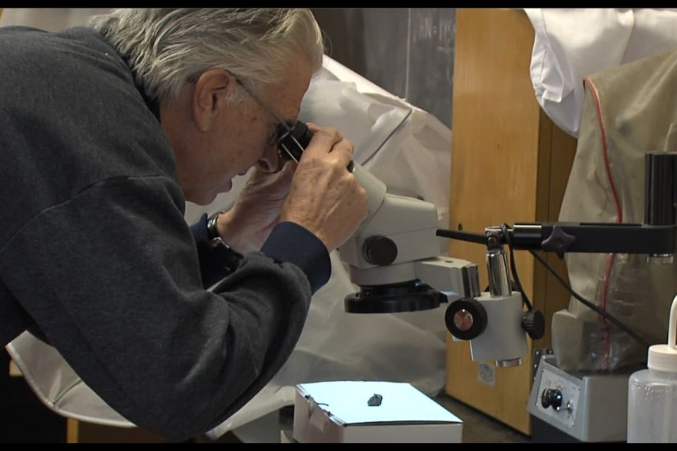 Stephen Kissin, a geology professor at Lakehead University examines fragments collected from a possible meteorite strike on Highway 61 on Dec. 13. (Jonathan Wilson - TBT News).