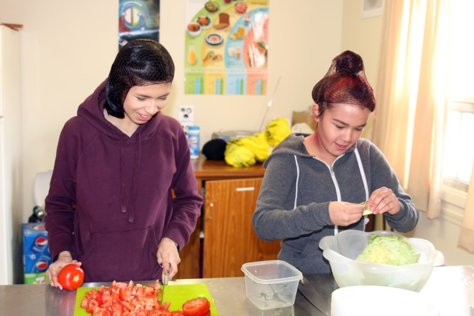 Leila Nattinen and Michelle King, members of the Vale/Limbrick Youth Council, were busy getting things ready on Saturday for the Indian taco and bannock burger fundraiser organized by the Vale/Limbrick Community Action Group.