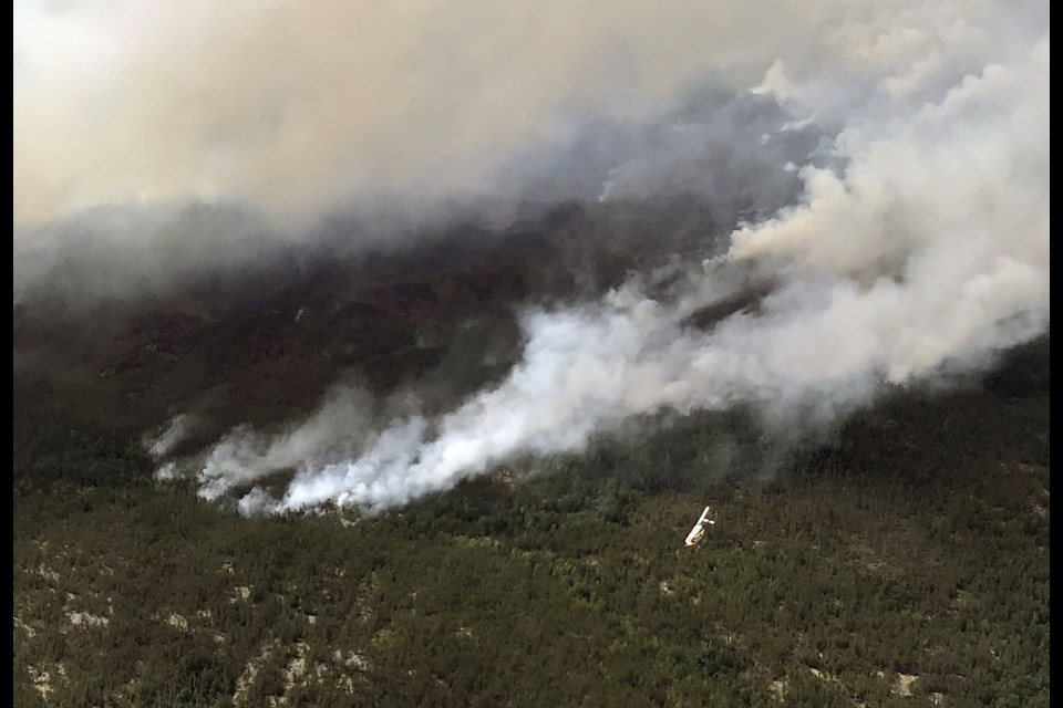 Looking down at a helicopter engaged in the suppression of Kenora Fire 71. (MNRF).